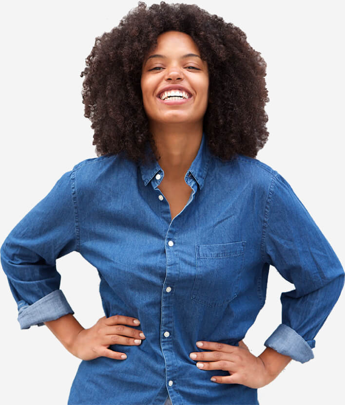 A female established business owner wearing a denim button down shirt with her hands on her hips